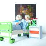 Pflegekraft steht hinter Pflegebett